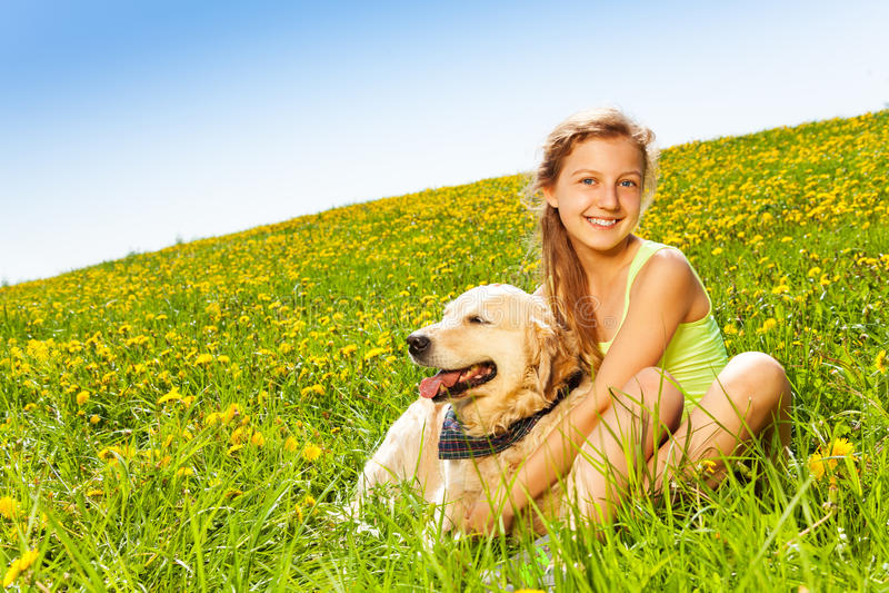 Umarmungshund des netten glücklichen Mädchens im Sommer lizenzfreie stockfotografie