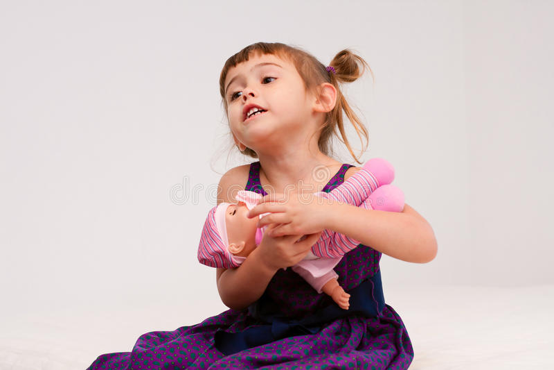 Umarmungspuppe des kleinen Mädchens stockbild