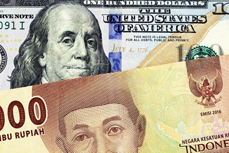 Umas cem notas de dólar americana com uma nota indonésia de cinco rupias foto de stock royalty free
