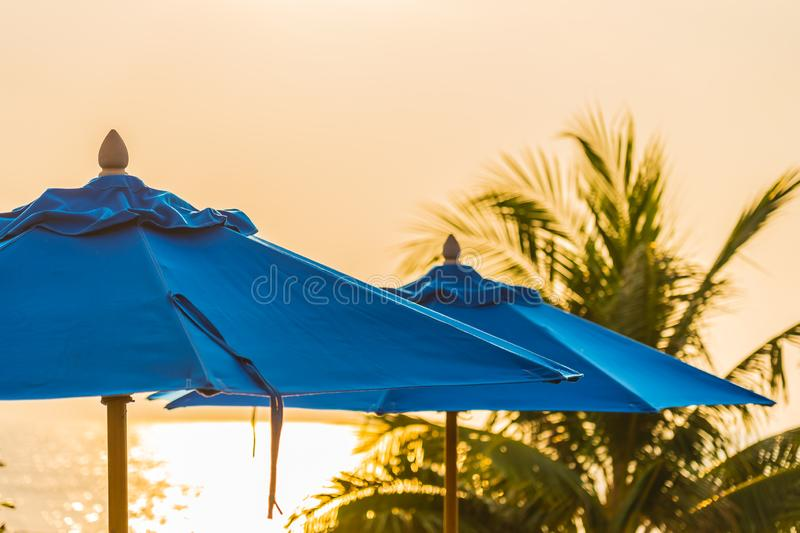 Umbrella around swimming pool in hotel and resort neary sea ocean and beach for leisure travel. Empty chair and umbrella around swimming pool in hotel and resort royalty free stock photo