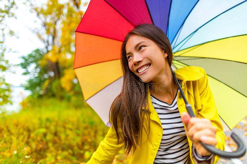 Umbrella Autumn Fashion lifestyle Asian woman under colorful umbrella on fall rainy day , happy girl enjoying walk under the rain. In forest with yellow leaves royalty free stock images