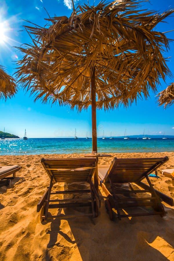 Umbrella with beach chairs stock photos
