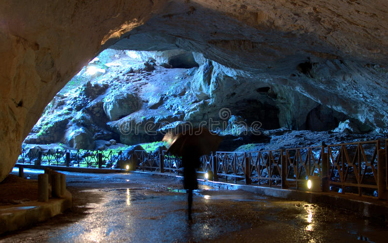 With umbrella in the cave. A visitor fitted with umbrella walking in the caves of St. John of Domusnovas (Sardinia). The cave has been recognized as a Natural stock photo