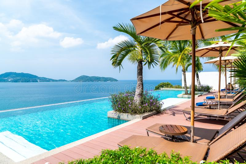 Umbrella and chair around swimming pool in hotel and resort. Holiday Vacation concept royalty free stock images