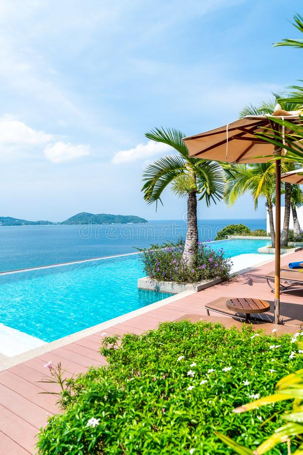 Umbrella and chair around swimming pool in hotel and resort. Holiday Vacation concept stock photos