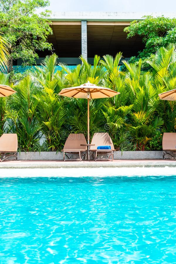 Umbrella and chair around swimming pool in hotel and resort. Holiday Vacation concept stock photo