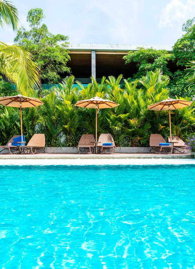 Umbrella and chair around swimming pool in hotel and resort. Holiday Vacation concept royalty free stock image