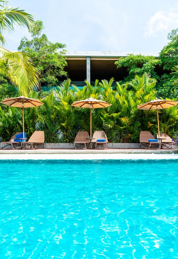 Umbrella and chair around swimming pool in hotel and resort. Holiday Vacation concept stock photography