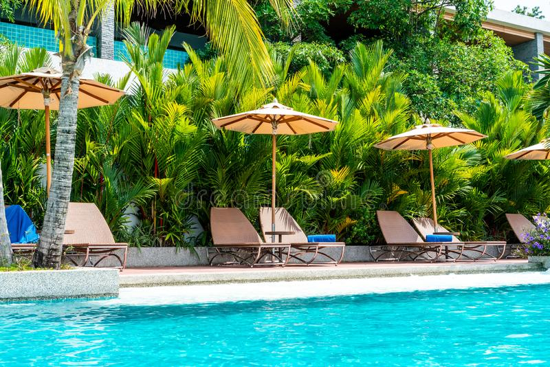 Umbrella and chair around swimming pool in hotel and resort. Holiday Vacation concept royalty free stock photo