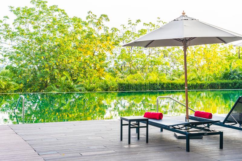 Umbrella and chair around swimming pool in hotel resort. For leisure vacation and travel royalty free stock photography