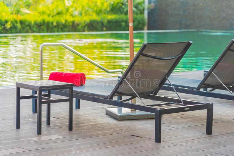 Umbrella and chair around swimming pool in hotel resort. For leisure vacation and travel royalty free stock photos