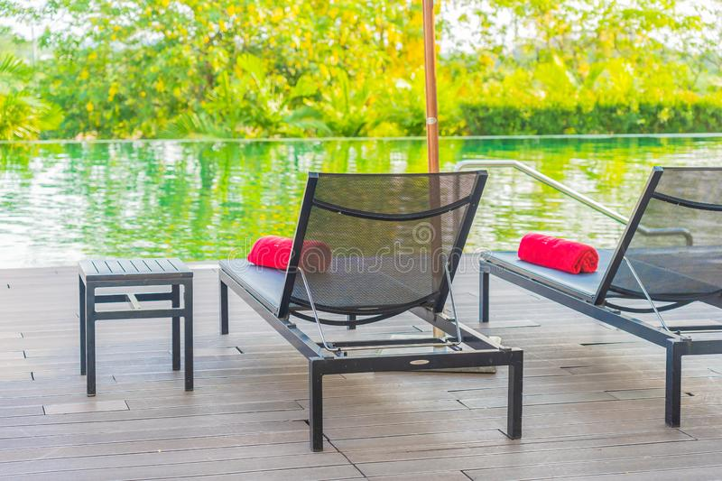 Umbrella and chair around swimming pool in hotel resort. For leisure vacation and travel stock photography