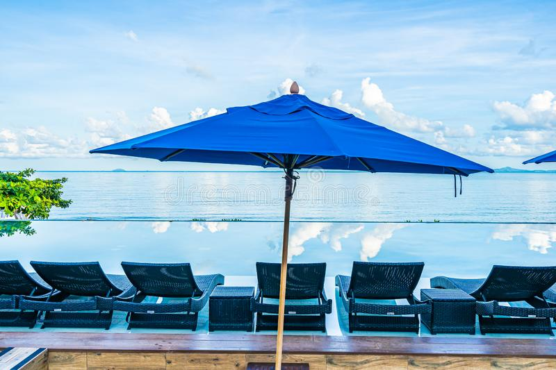 Umbrella and chair around swimming pool in hotel resort neary sea ocean beach for leisure relax in holiday. Vacation royalty free stock photo