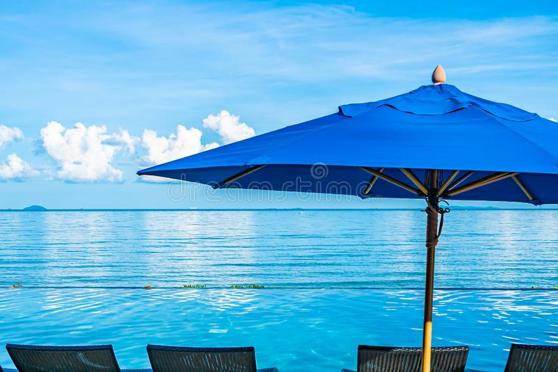 Umbrella and chair around swimming pool in hotel resort neary sea ocean beach for leisure relax in holiday. Vacation royalty free stock image
