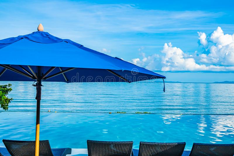 Umbrella and chair around swimming pool in hotel resort neary sea ocean beach for leisure relax in holiday. Vacation stock images
