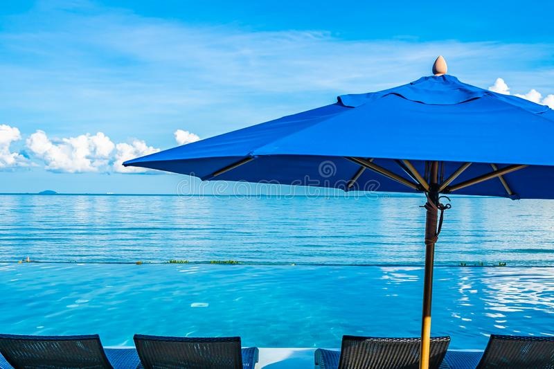 Umbrella and chair around swimming pool in hotel resort neary sea ocean beach for leisure relax in holiday. Vacation royalty free stock images