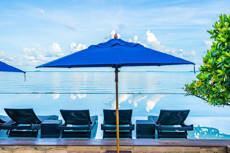 Umbrella and chair around swimming pool in hotel resort neary sea ocean beach for leisure relax in holiday. Vacation stock photos