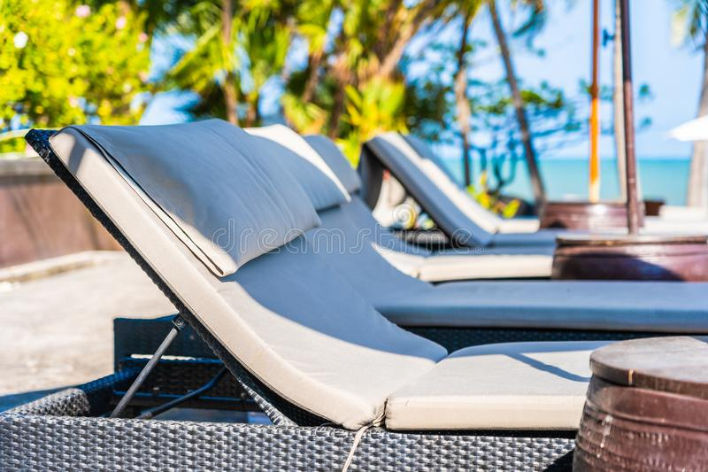 Umbrella and chair around swimming pool in hotel resort neary sea ocean beach for vacation. Umbrella and chair around swimming pool in hotel resort neary sea royalty free stock photos