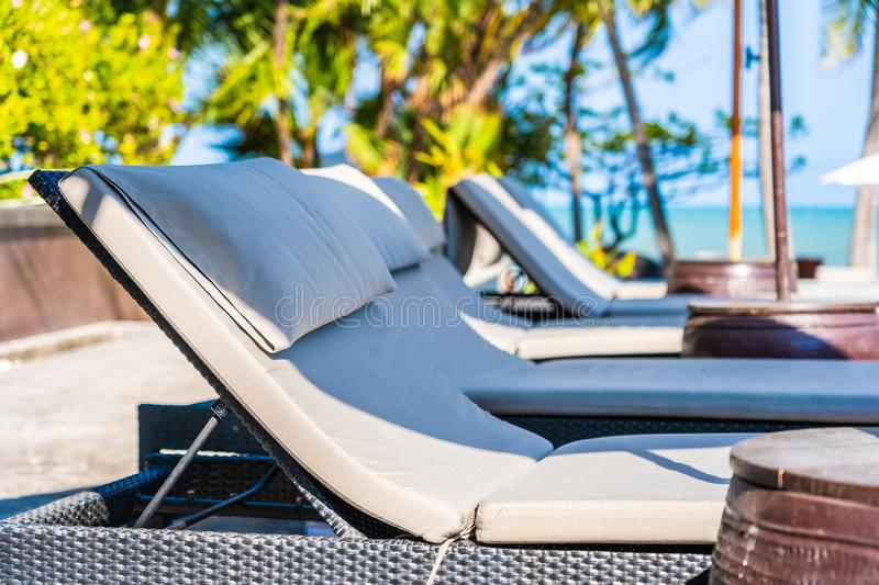 Umbrella and chair around swimming pool in hotel resort neary sea ocean beach for vacation. Umbrella and chair around swimming pool in hotel resort neary sea royalty free stock image