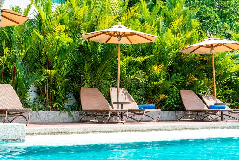 Umbrella and chair around swimming pool in hotel and resort. Holiday Vacation concept stock image