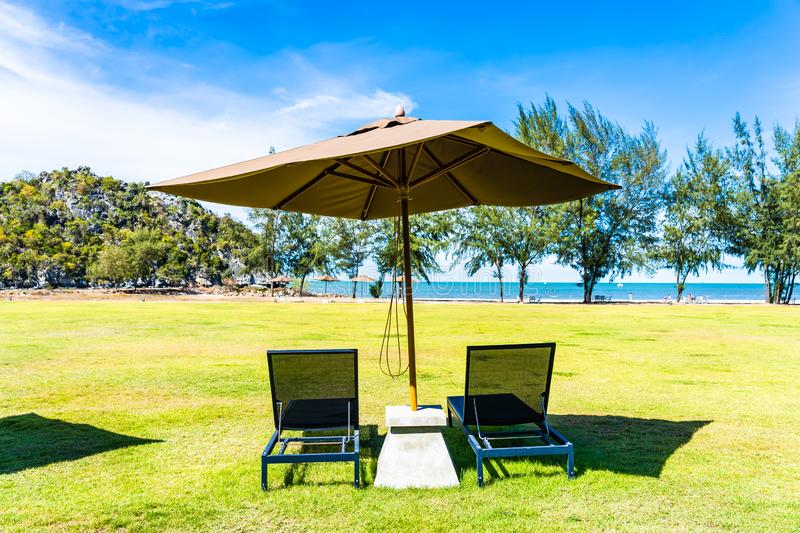 Umbrella and chair on the green grass nearly sea beach stock photo