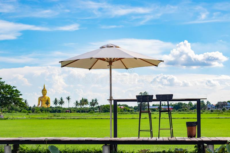 Umbrella and coffee table at rice field. Big buddha stock image