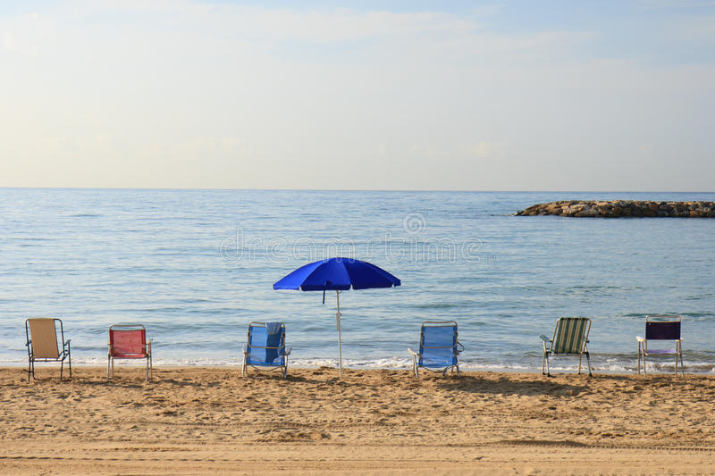 Umbrella and colorful chairs on the beach stock photography