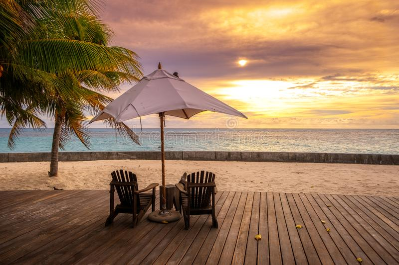 Umbrella and deck chairs on the beautiful tropical beach and sea at sunset time for travel and vacation royalty free stock photos