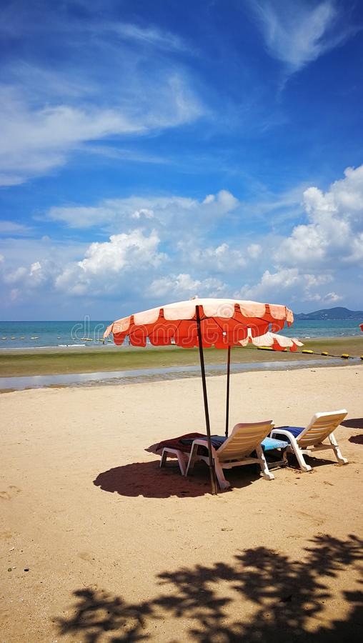 Umbrella and deckchair on a beach in Thailand stock images