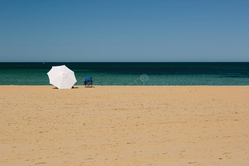 Umbrella and deckchair on Mordialloc Beach, Melbourne. Mordialloc Beach in Melbourne. A large white umbrella near the waterline shelters its occupants stock photos