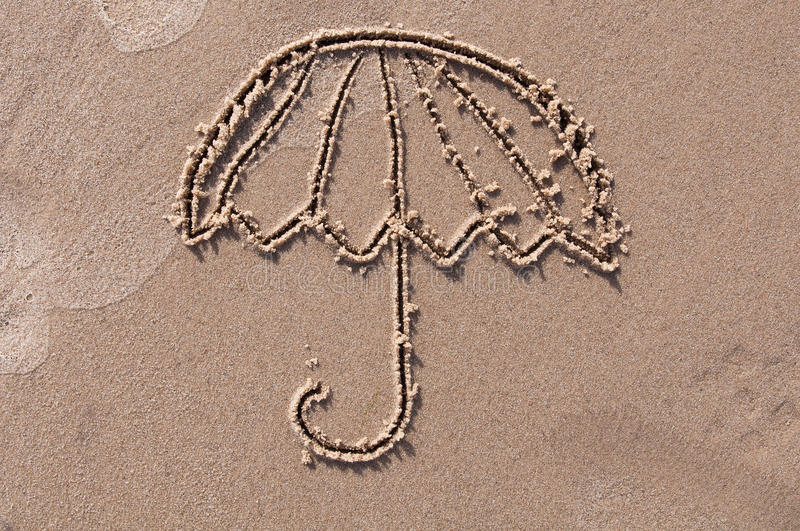 Umbrella drawn in the sand. Beach background. Top view royalty free stock photos