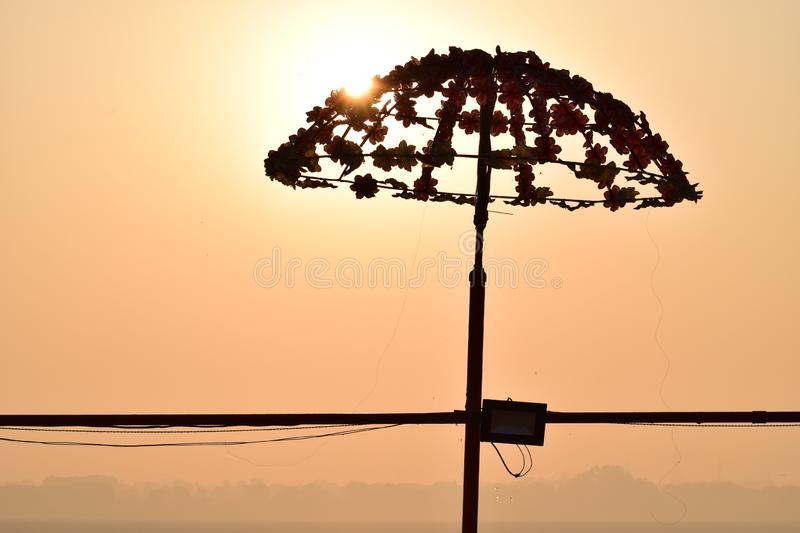 Sun rise behind umbrella. Desi umbrella at Assi ghat Varanasi, UP India in the morning of spring , morning  shadow , Sun rising behind the umbrella stock photos