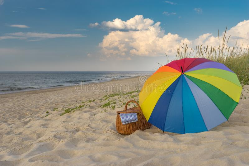 Umbrella and picnic basket against wild beach stock image