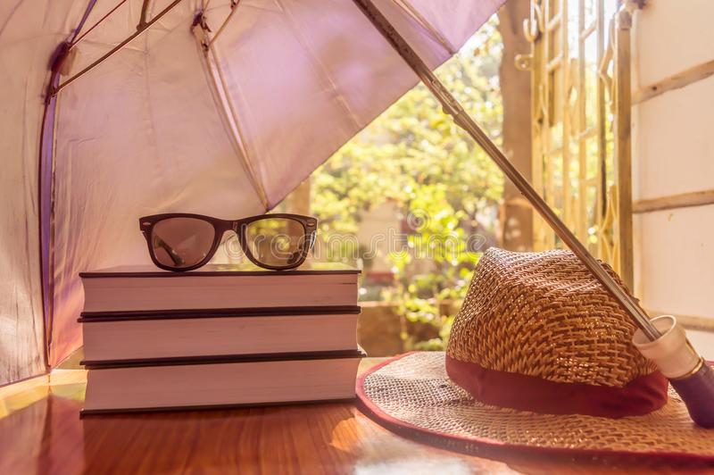 Umbrella protecting beautiful woman things. Books sunglasses and a straw hat. Summer holiday concept with copy space room for text. Sunburn risk concept protect stock image