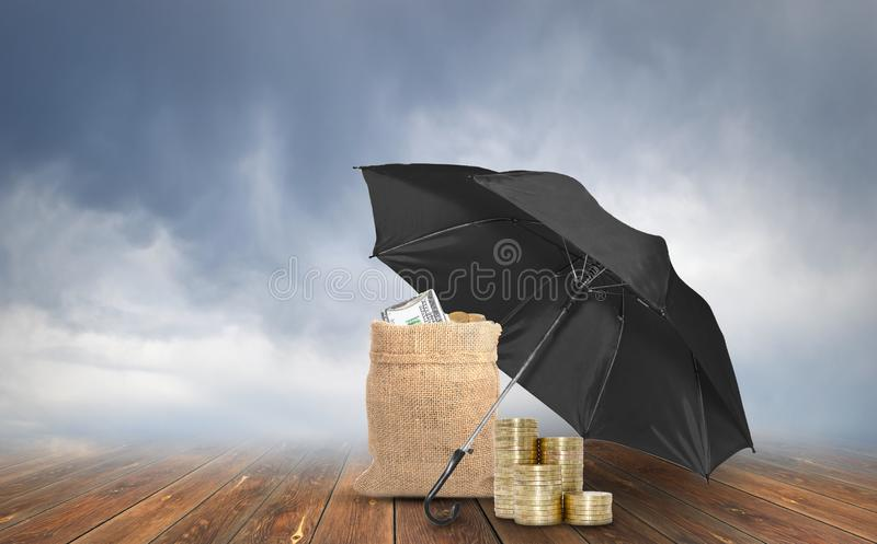Umbrella protection bag with dollars and stack of coins on rainy weather background . Protection money royalty free stock photos