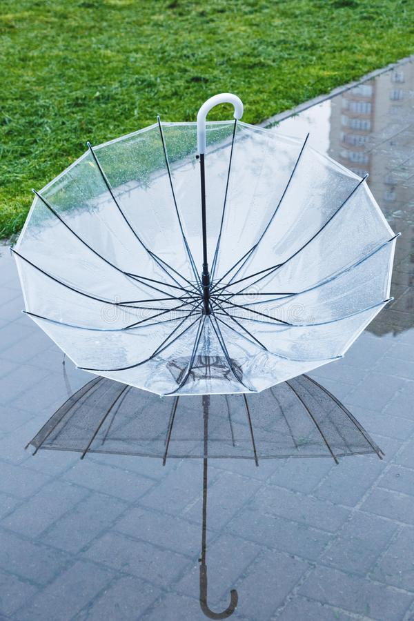 Umbrella in the puddle with reflection in the water after the rain. Rainy weather. At spring royalty free stock images