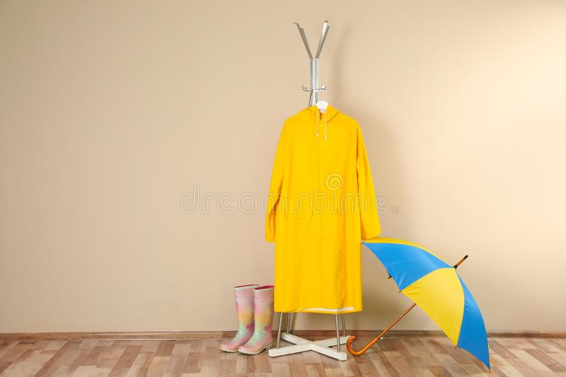 Umbrella, rain coat and rubber boots near beige wall. Space for text royalty free stock image