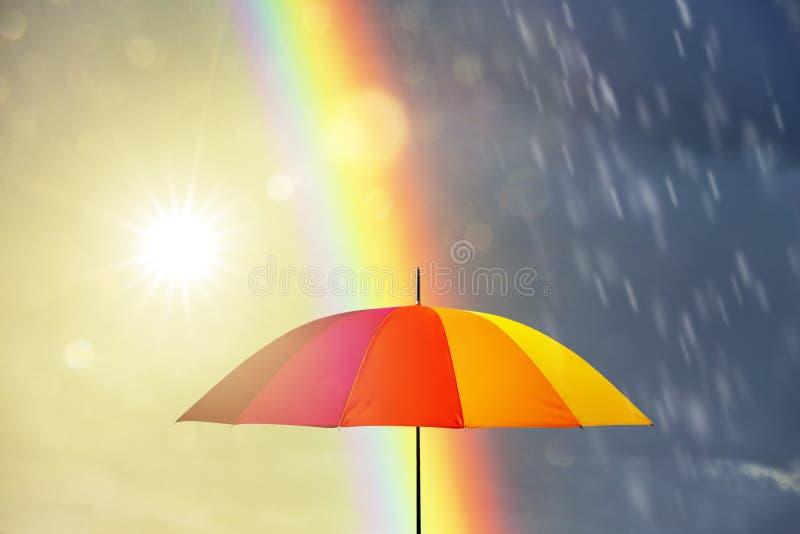 Umbrella at a rainy day with rainbow royalty free stock image