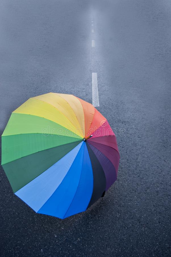 Umbrella on the road. Colorful umbrella lying on empty road, vertical, close up