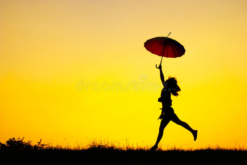 Umbrella Woman Jump And Sunset Silhouette Stock Image