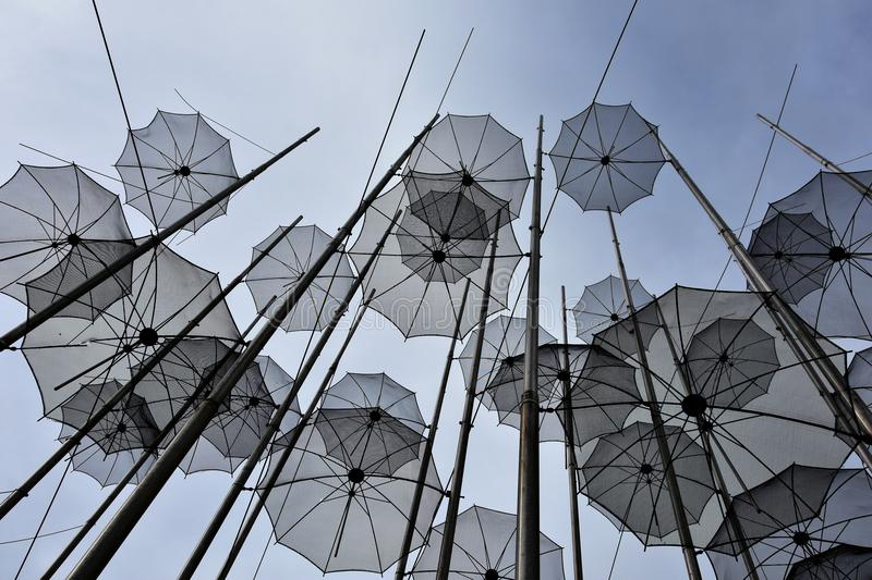 Umbrellas at the beach, sculpture of Giorgos Zongolopoulos. Umbrellas at the waterfront of Thessaloniki, Greece, under a blue sky. The artist is the greek stock images