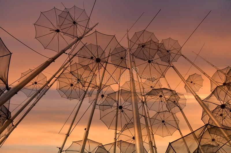 Umbrellas at the beach, sculpture of Giorgos Zongolopoulos. Umbrellas at the waterfront of Thessaloniki, Greece, at sunrise at early morning. The artist is the royalty free stock image