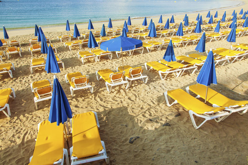 Umbrellas and empty beach couches stock images