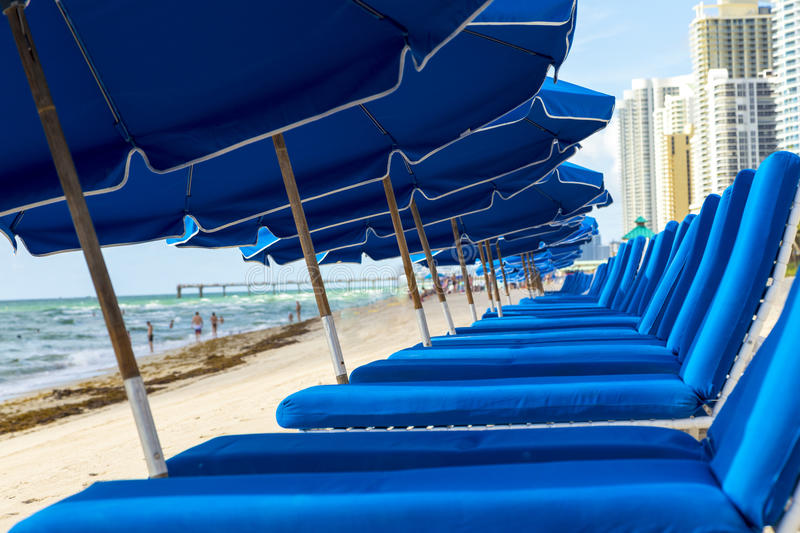 Umbrellas and empty beach couches stock photography