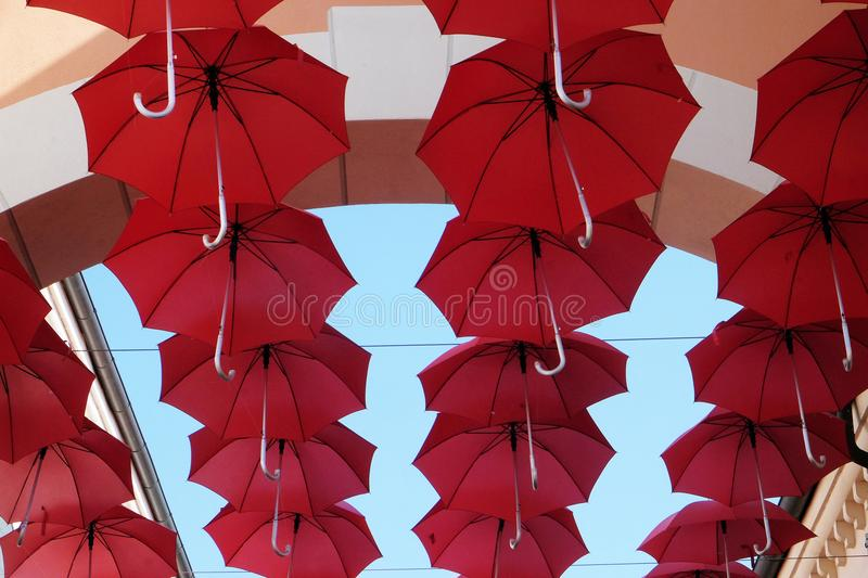 Umbrellas flying in sky over city street in Venice stock images