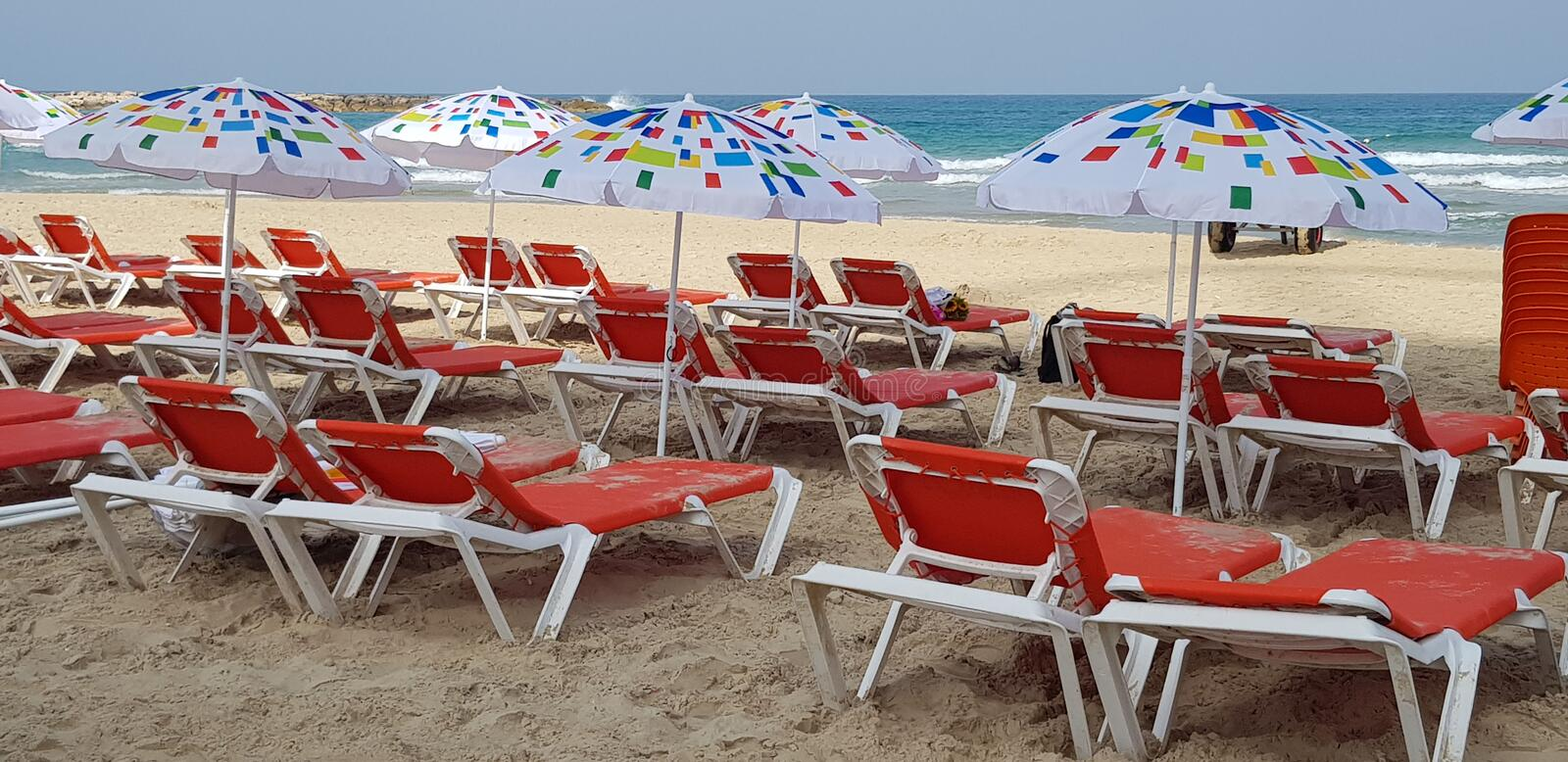 Umbrellas and orange chairs on the beach near the sea royalty free stock photo