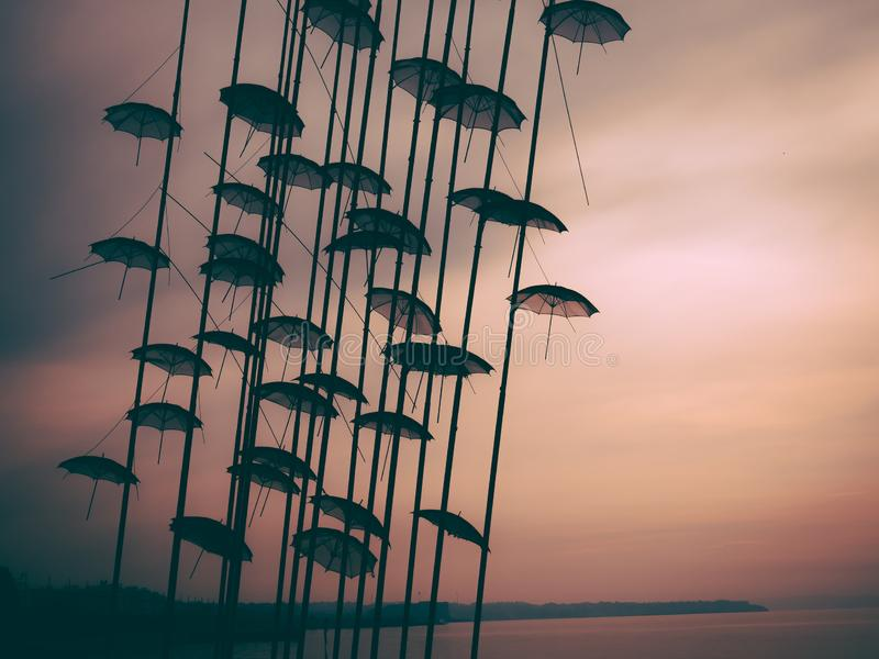 Umbrellas sculpture in a foggy sunset -  Thessaloniki, Greece royalty free stock image