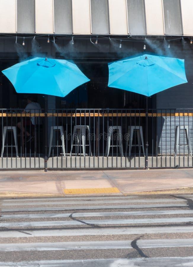 Umbrellas at the sidewalk saloon. Blue umbrellas at a sidewalk bar, Lake Havasu City, Arizona stock photos