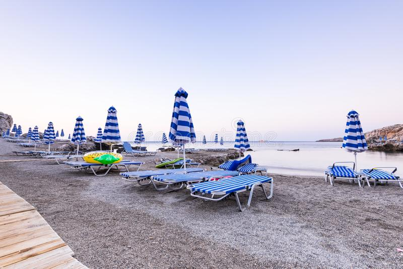Umbrellas and Sun Beds at Pebble Beach at Sunrise, Rhodes, Греция стоковые фото