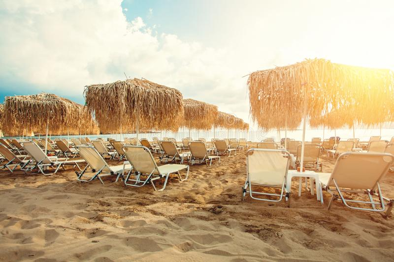 Umbrellas and sunbeds on sea beach against sky clouds background. Summer holiday concept stock photography